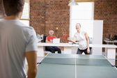 Man and woman in office space playing ping pong — Stock Photo