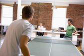 Two men in office space playing ping pong — Stock Photo