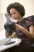 Woman sitting in computer room punching a small punching bag — Stock Photo