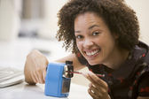 Woman in computer room using pencil sharpener and smiling — Stock Photo
