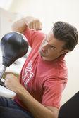Man indoors using small punching bag — Stock Photo