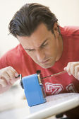 Man indoors using pencil sharpener — Stock Photo
