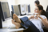 Woman in computer room with feet up drinking coffee — Stock Photo