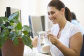 Woman in computer room watering plant smiling — Stock Photo