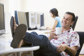 Man in computer room with feet up drinking coffee and smiling — Stock Photo