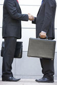 Two businessmen holding briefcases outdoors shaking hands — Stock Photo