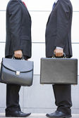 Two businessmen holding briefcases outdoors — Stock Photo