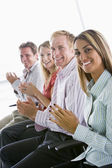Four businesspeople applauding indoors smiling — Stock Photo