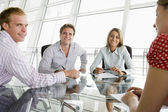 Four businesspeople in a boardroom with paperwork smiling — Stock Photo