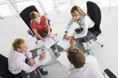 Four businesspeople in a boardroom with paperwork — Stock Photo