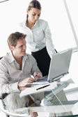 Two businesspeople in boardroom with laptop — Stock Photo