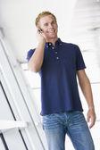 Man standing in corridor wearing headset smiling — Stock Photo