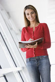 Woman standing in corridor with personal organizer smiling — Stock Photo