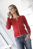 Woman standing in corridor using cellular phone smiling — Stock Photo