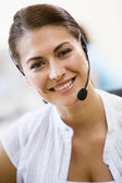 Woman wearing headset indoors smiling — Stock Photo