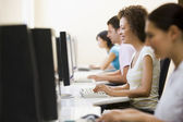 Four in computer room typing and smiling — Stock Photo
