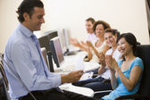 Man with clipboard giving lecture in applauding computer class — Stock Photo