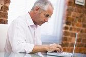 Podnikatel, sedí v kanceláři, psaní na notebooku — Stock fotografie