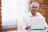 Businessman sitting in office on laptop smiling — Stock Photo