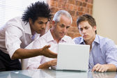 Three businessmen sitting in office with laptop — Stock Photo