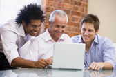 Three businessmen sitting in office with laptop smiling — Stock Photo