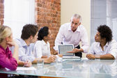 Five businesspeople in boardroom with laptop — Stock Photo