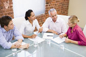 Four businesspeople in boardroom talking — Stock Photo