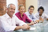 Four businesspeople in boardroom smiling — Stock Photo
