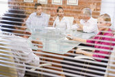 Five businesspeople in boardroom through window — Stock Photo