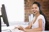 Kulaklık takmış ve bilgisayar s yazarak office iş kadını — Stok fotoğraf