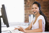Businesswoman in office wearing headset and typing on computer s — Stock Photo