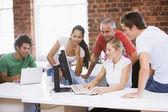 Fem företagare i kontorslokaler på datorn och smil — Stockfoto