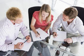 Three businesspeople in boardroom with paperwork — Stock Photo