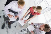 Three businesspeople in boardroom with paperwork — Stockfoto