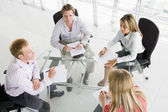 Four businesspeople in boardroom with paperwork — Stock Photo