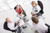 Four businesspeople in boardroom with paperwork smiling — Stock Photo