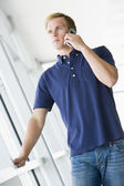 Man standing in corridor smiling using cellular phone — Stock Photo