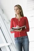 Woman standing in corridor writing in personal organizer — Stock Photo