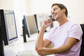 Man sitting in computer room using cellular phone and smiling — Stock Photo