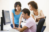 Three sitting in computer room looking at monitor — Stock Photo