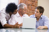 Three businessmen in office with laptop talking — Stock Photo