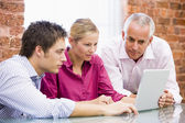 Three businesspeople in office looking at laptop — Stock Photo