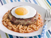 Corned Beef Hash Cake with Alphabet Pasta and a Fried Egg — Stock Photo