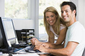 Couple in home office with computer smiling — Stock Photo