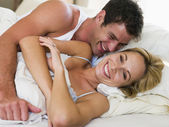 Couple in bed laughing — Stock Photo