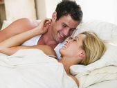Couple in bed smiling — Stock Photo