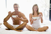 Couple sitting in bed eating cereal and smiling — Stock Photo