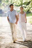 Couple walking outdoors holding hands and smiling — Stock Photo