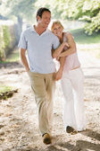 Couple walking outdoors arm in arm smiling — Stock Photo