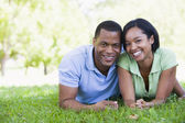 Couple lying outdoors smiling — Stock Photo